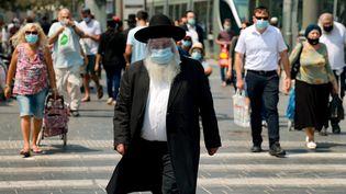 Un Juif ultra-orthodoxe porte un masque et une visière contre le coronavirus dans les rues de Jérusalem, le 11 septembre 2020. (EMMANUEL DUNAND / AFP)