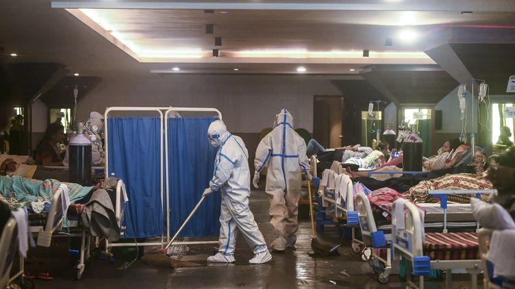 Une personne nettoie le sol d'une salle des fêtes convertie en hôpital de campagne, le 1er mai 2021, à New Delhi (Inde). (PRAKASH SINGH / AFP)