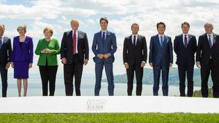 Les sept dirigeants présents lors du G7 organisé à La Malbaie (Canada), le 8 juin 2018, entourés par le président du Conseil européen, Donald Tusk, et le président de la Commission européenne, Jean-Claude Juncker. (HANDOUT / THIERRY QUENETTE / ANADOLU AGENCY / AFP)