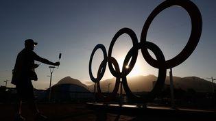 Un journaliste photographie les anneaux olympiques à Rio de Janeiro (Brésil), le 31 juillet 2016. (CHRISTIAN PETERSEN / GETTY IMAGES NORTH AMERICA / AFP)