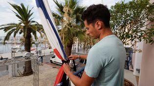 Le 6 août 2019, un employé communal de la ville de Sanary (Var) met en berne le drapeau de la mairie, après la mort du maire de Signes (MAXPPP)