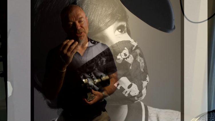 Eric Traversié devant l'un de ses portraits masqués. (France 3 Aquitaine / E. Gonzalez)