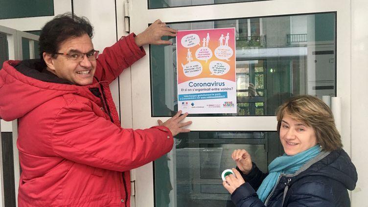 Le créateur de la Fête des voisins Atanase Perifan a collé des affiches sur les portes d'immeuble pour rappeler l'importance de la solidarité entre voisins, le 4 mars 2020. (EMELINE FERRY / FRANCE-BLEU PARIS)