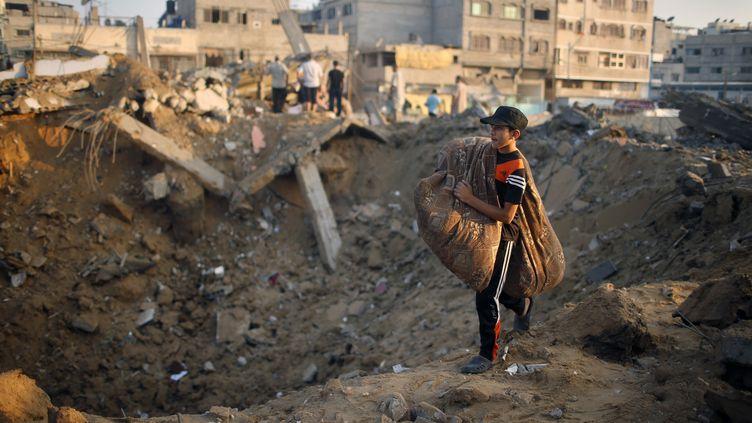 Un enfant emporte ses affaires après la destruction de sa maison à Gaza par un raid israélien, le 9 juillet 2014. (MOHAMMED SALEM / REUTERS)