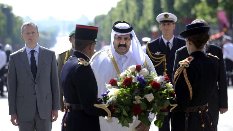 Le ministre de l'Agriculture Bruno Le Maire lors d'une cérémonie sur la tombe du soldat inconnu à Paris, le 23 juin 2009, en compagnie de l'émir du QatarSheikh Hamad Bin Khalifa Al-Thani. (STEPHANE DE SAKUTIN / AFP)