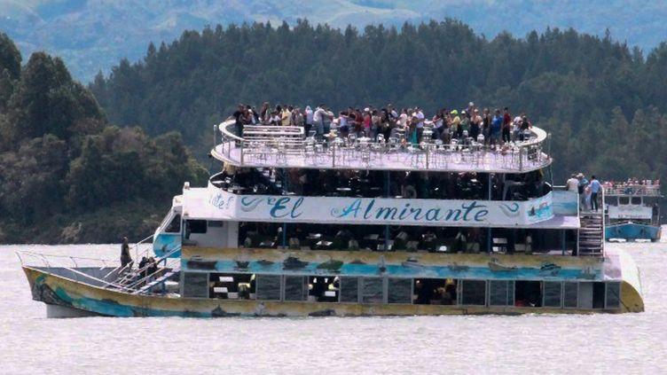 """Le bateau de tourisme """"Almirante"""", juste avant son naufrage, dimanche 25 juin 2017,sur un lac du nord-ouest de la Colombie. (JUAN QUIROZ / AFP)"""