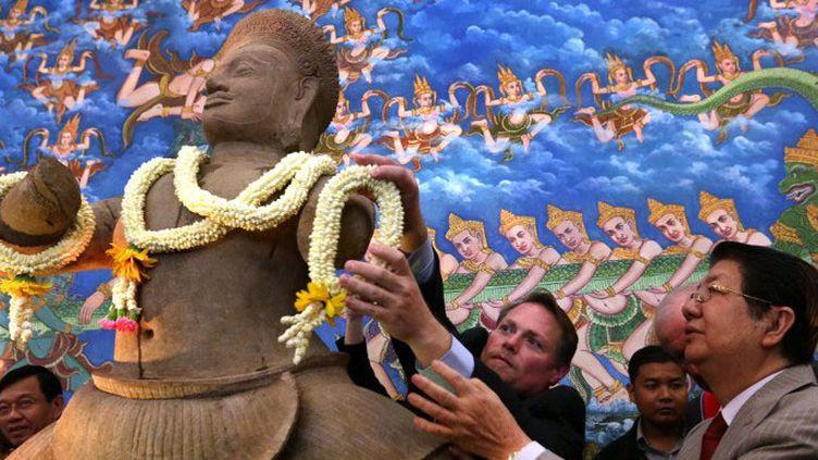 """Le premier ministre cambodgienSok An accueille le retour de la statue""""Duryodhana bondissant"""" à Phnom Penh le 3 juin 2014, après 40 ans d'absence, suite à un vol au début des années 1970  (CHARLY TWO / AFP)"""