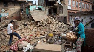 Des Népalais fouillent les décombres d'une habitation détruite par le séisme, le 2 mai 2015 à Katmandou (Népal). (MENAHEM KAHANA / AFP)
