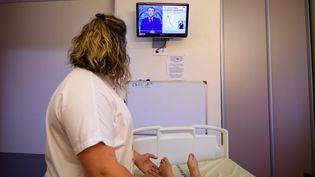 Une infirmière regarde l'allocution d'Emmanuel Macron, lundi 12 juillet 2021, depuis son hôpital. (PHOTOPQR/LA MONTAGNE/MAXPPP)