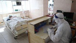 Un soignant s'occupe d'un patient atteint de Covid-19 dans un hôpital de Volgograd, en Russie, le 18 août 2021. (KIRILL BRAGA / SPUTNIK / AFP)