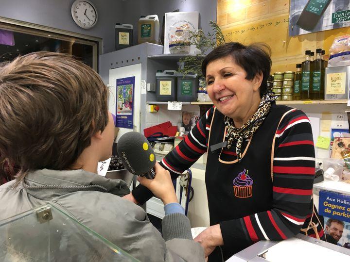 Paul interviewe Lolita, commerçante à la Halle de Nîmes. (INGRID POHU / RADIO FRANCE)