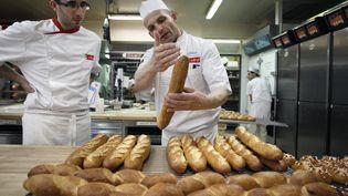 Un apprenti écoute son professeur sur la baguette qu'il vient de sortir du four à l'Institut national de boulangerie et de pâtisserie, à Rouen (Seine-Maritime), le 20 novembre 2012. (CHARLY TRIBALLEAU / AFP)