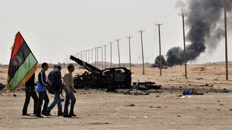 Des insurgés défilent devant un char des forces loyalistes libyennes carbonisé près d'Aldjabiya reprise le 26 mars 2011 (AFP/ARIS MESSINIS)