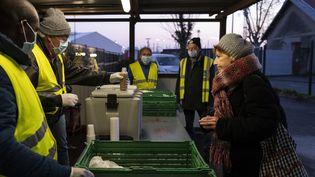 Des membres du Secours catholique distribuent un petit-déjeuner à des personnes dansle besoin à Toulouse (Haute-Garonne), le 3 avril 2020, lors du premier confinement. (LIONEL BONAVENTURE / AFP)