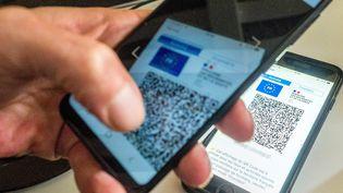 Une personne scanne un pass sanitaire avec son smartphone, le 29 septembre 2021 (illustration). (BRUNO LEVESQUE / MAXPPP)