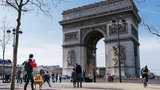Des passants se promènent à Paris, près de l'Arc de Triomphe, le 21 février 2021. (MATHIEU MENARD / HANS LUCAS / AFP)