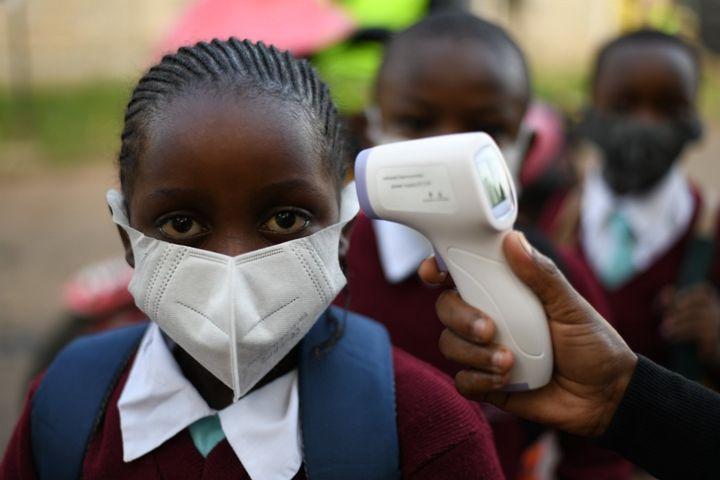 Prise de température de tous les élèves avantleur entré dans l'école Our Lady of Mercy de Nairobi, le 4 janvier 2021.  (SIMON MAINA / AFP)