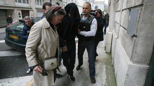 Le principal suspect dans la mort du jeune Alexandre Junca, un homme de 27 ans (C), la tête recouverte d'une bâche, accompagné par son avocate Carine Magne (G) arrive, le 07 avril 2013 au palais de justice de Pau (THIERRY SUIRE / AFP)