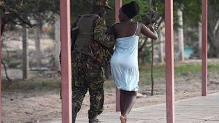 Un membre des forces de sécurité escorte une étudiante, sur le campus de Garissa (Kenya), après l'attaque des shebabs islamistes, jeudi 2 avril 2015. (CARL DE SOUZA / AFP)