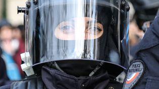 Une policière casquée se tient près des Champs-Elysées. (ZAKARIA ABDELKAFI / AFP)