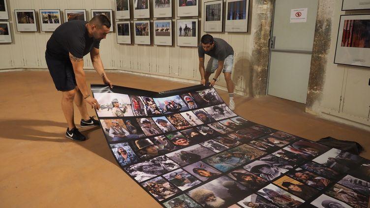 Les préparatifs de la partie de l'exposition consacrée au photographe français Patrick Chauvel à Visa pour l'image. (RAYMOND ROIG / AFP)