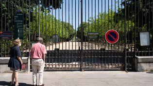 Deux personnes devant la grille fermée du jardin du Luxembourg, à Paris, le 26 avril 2020. (LAURE BOYER / HANS LUCAS / AFP)