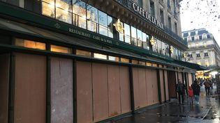 """À Paris, quartier de l'Opera, des commerçants protègent leurs vitrines vendredi 7 décembre veille de mobilisation des """"gilets jaunes"""". Ils resteront rideaux baissés samedi. (XAVIER MEUNIER / FRANCE-INFO)"""