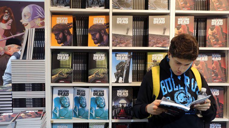 Un garçon en pleine lecture d'une BD américaine au Festival de la BD d'Angoulème en 2014  (NICOLAS TUCAT / AFP)