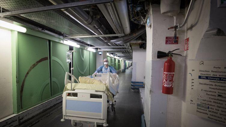 Un soignant transporte un lit médicalisé dans les services de réanimation de l'hôpital Lariboisière, à Paris, en avril 2020. (JOEL SAGET / AFP)