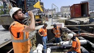 Un salarié du BTP boit de l'eau en plein soleil. Photo d'illustration. (MARC OLLIVIER / MAXPPP)