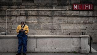 Un homme seul, à l'entrée du métro, porte un masque de protection et regarde son téléphone portable. (PHILIPPE LOPEZ / AFP)