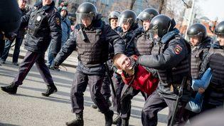 Des policiers russes emmènent un manifestant, le 26 mars 2017 à Moscou(Russie), lors d'une manifestation contre la corruption. (ALEXANDER UTKIN / AFP)