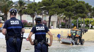 Des policiers surveillent une plage à La Ciotat, Bouches-du-Rhônes, le 17 juin 2011. (ANNE-CHRISTINE POUJOULAT / AFP)