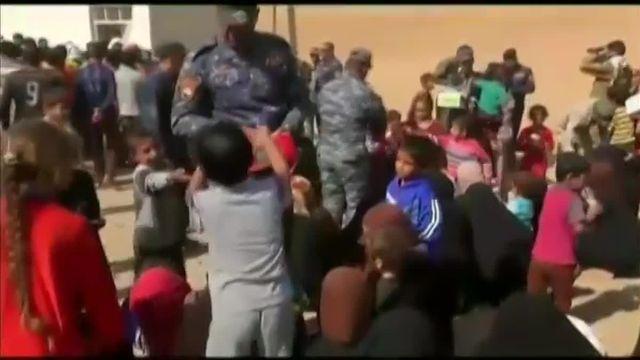Au sud de Mossoul, des milliers d'Irakiens reçoivent la nourriture des mains des policiers
