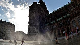 Des enfants jouent dans une fontaine à Strasbourg (Bas-Rhin), le 2 juillet 2015. (PATRICK HERTZOG / AFP)
