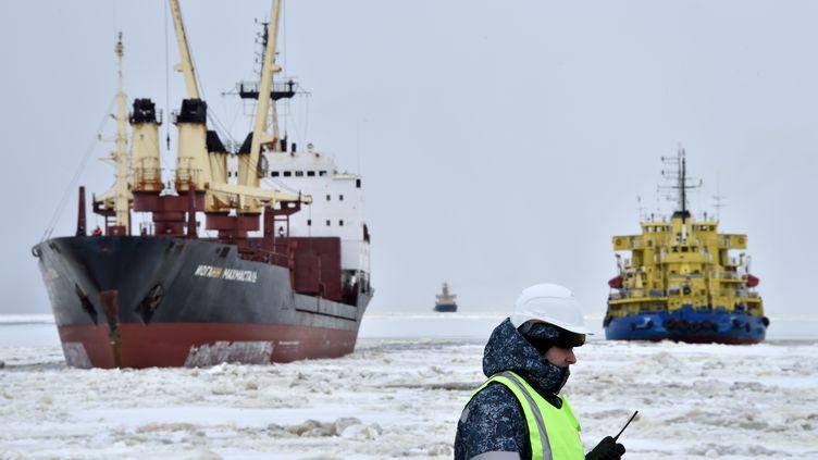 Un navire brise-glace devant un porte-conteneurs dans le cercle arctique, en mai 2016. (KIRILL KUDRYAVTSEV / AFP)