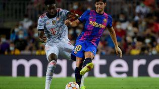 Alphonso Davies et Sergi Roberto à la lutte pour le ballon lors de Barcelone-Bayern Munich, le 14 septembre 2021 au Camp Nou. (LLUIS GENE / AFP)
