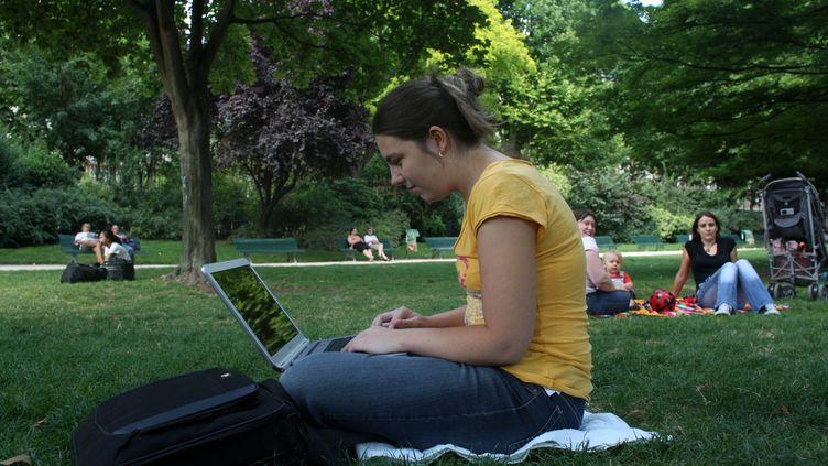Une femme travaille sur son ordinateur pendant qu'elle est dans un parc (le parc Monceau) à Paris. (MAXPPP)