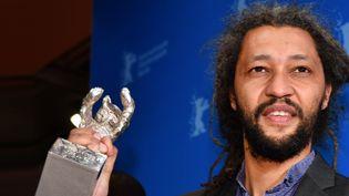 """Le réalisateur franco-sénégalais Alain Gomis reçoit l'Ours d'Argent pour """"Félicité"""" à la Berlinale, samedi 18 février 2017.  (Jens Kalaene / DPA / AFP)"""