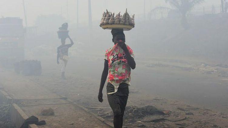 Les vendeurs se couvrent le nez pour marcher dans les décharges du site d'Olusosun à Ojota, près de Lagos, capitale commerciale du Nigeria, le 22 mars 2018. Le gouvernement a fermé le site après un incendie dû à une flambée de gaz piégés. (PIUS UTOMI EKPEI/AFP)