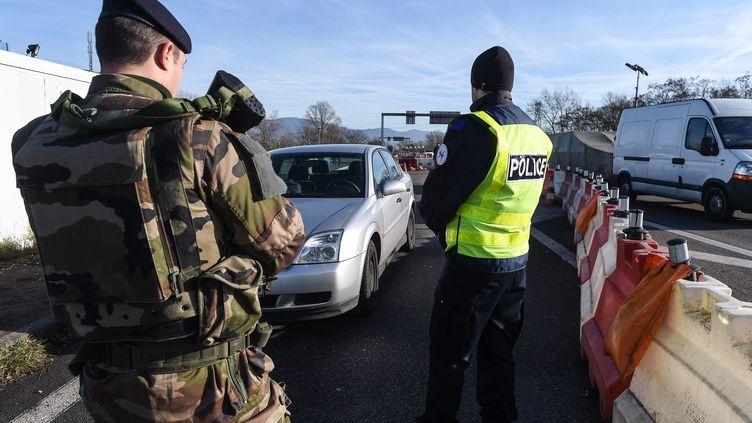Un militaire et un policier contrôlant les voitures à la frontière avec l'Allemagne, le 22 décembre 2016, trois jours après l'attentat de Berlin. (SEBASTIEN BOZON / AFP)