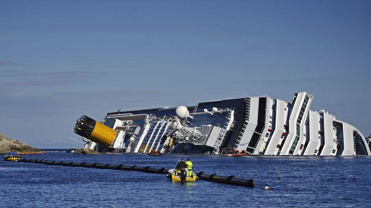 """L'épave du """"Concordia"""" le 26 janvier 2012 au large de l'île du Giglio en Italie. (FILIPPO MONTEFORTE / AFP)"""
