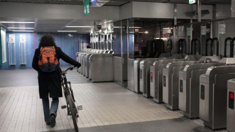 Un homme embarque son vélo à la station Les Halles, dans le métro parisien, le 28 janvier 2009. (JACQUES DEMARTHON / AFP)