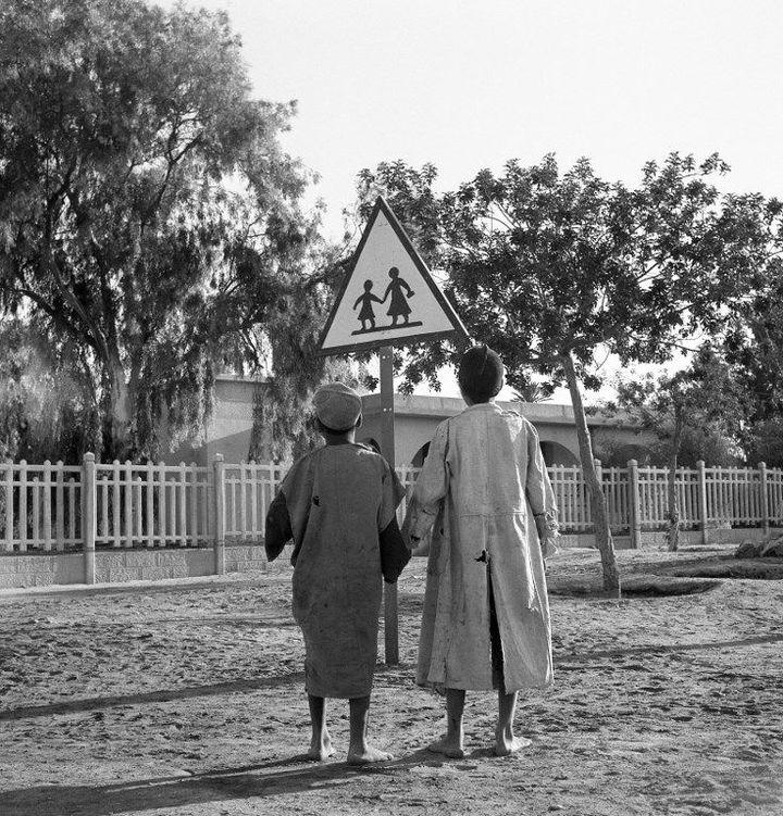 Deux enfants algériens, pieds nus, regardent un panneau de signalisation «Attention Ecole» dans le sud algérien en 1951. (Henri ELWING / INTERCONTINENTALE / AFP )