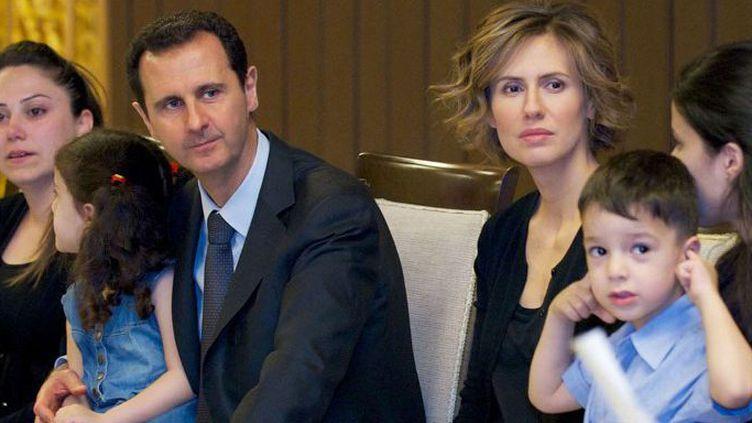 Le président syrien, Bachar al-Assad, et sa femme, Asma, rencontrent à Damas, le 29 avril 2014, des familles de Syriens tombés au combat pour la défense du régime. (AFP PHOTO/HO/THE OFFICIAL FACEBOOK PAGE OF THE SYRIAN PRESIDENCY)