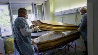 Des employés de pompes funèbres ferment un cercueil d'une victime du Covid-19 à l'hôpital de Mulhouse (Haut-Rhin) le 5 avril 2020. (SEBASTIEN BOZON / AFP)