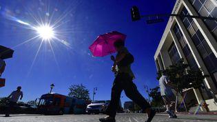 Un passant se protège du soleil le 24 octobre 2017 à Los Angeles (Etats-Unis) pendant une vague de chaleur. (FREDERIC J. BROWN / AFP)