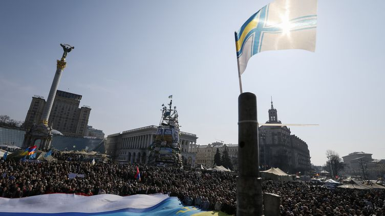 Un drapeau de la marine ukrainienne flotte au dessus d'un rassemblement antiguerre, sur la place Maïdan, à Kiev (Ukraine), le 23 mars 2014. (GLEB GARANICH / REUTERS)