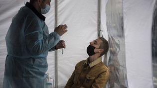 Un homme s'apprête à réaliser un test PCR, le 10 avril 2021 à Paris. (MAGALI COHEN / AFP)