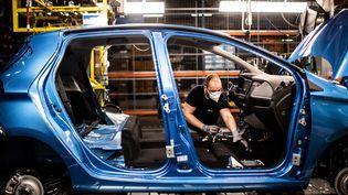 Unsalarié de Renault sur une ligne d'assemblage de l'usine de Flins (Yvelines), le 6 mai 2020. (MARTIN BUREAU / AFP)